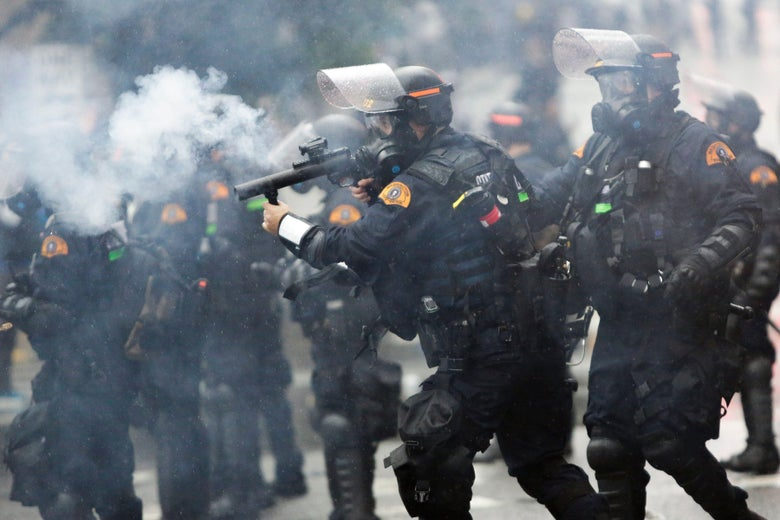 A row of officers in face shields, gas masks, and body armor firing tear gas canisters.