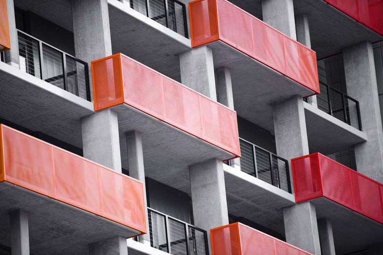 Orange and red balconies on a modern concrete high-rise building.