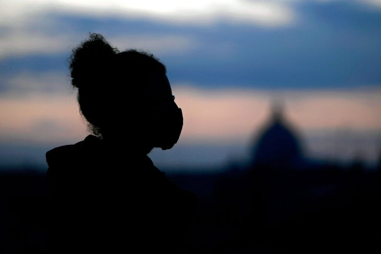 A person in a face mask at dusk