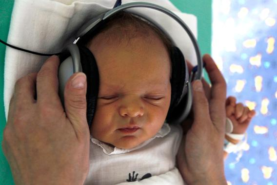 A nurse adjusts earphones playing relaxing music to a newborn baby in Kosice, east Slovakia May 2011.