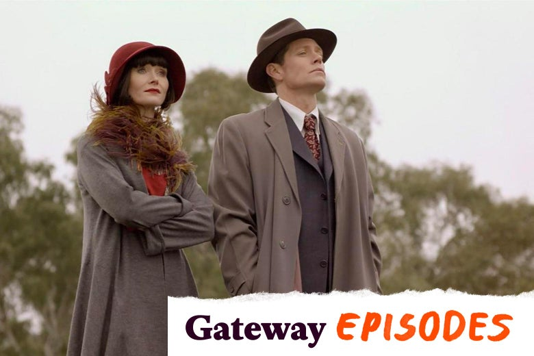 Essie Davis wears a red cloche hat and a fuzzy scarf, her hair cut in a blunt black bob. She stands next to Nathan Page, in a fedora and trench coat.