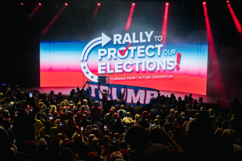 """Many people seated in an auditorium indoors. On the stage is a Trump sign and a screen that says """"Rally to Protect Our Elections Turning Point Action Convention."""""""