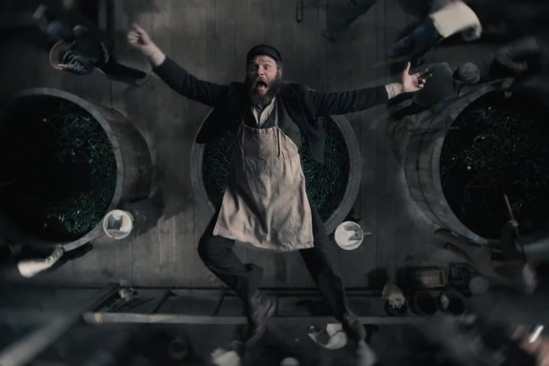 An overhead shot of Seth Rogen, in costume as a 1920s factory worker, falls backwards into a giant vat of pickles, arms outspread, screaming.