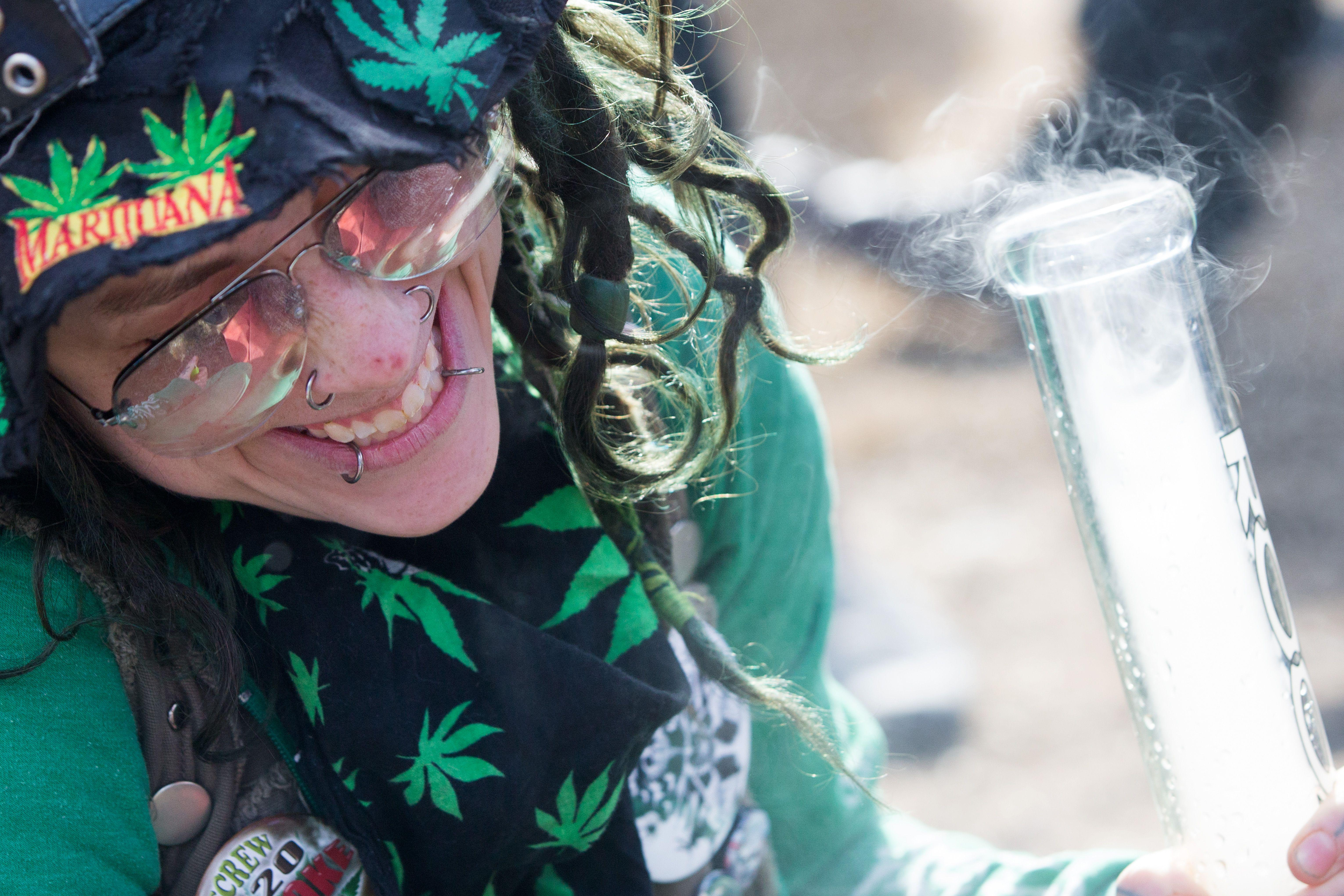 A woman inhales marijuana during the annual 4/20 rally on Parliament Hill in Ottawa, Ontario on April 20, 2018.