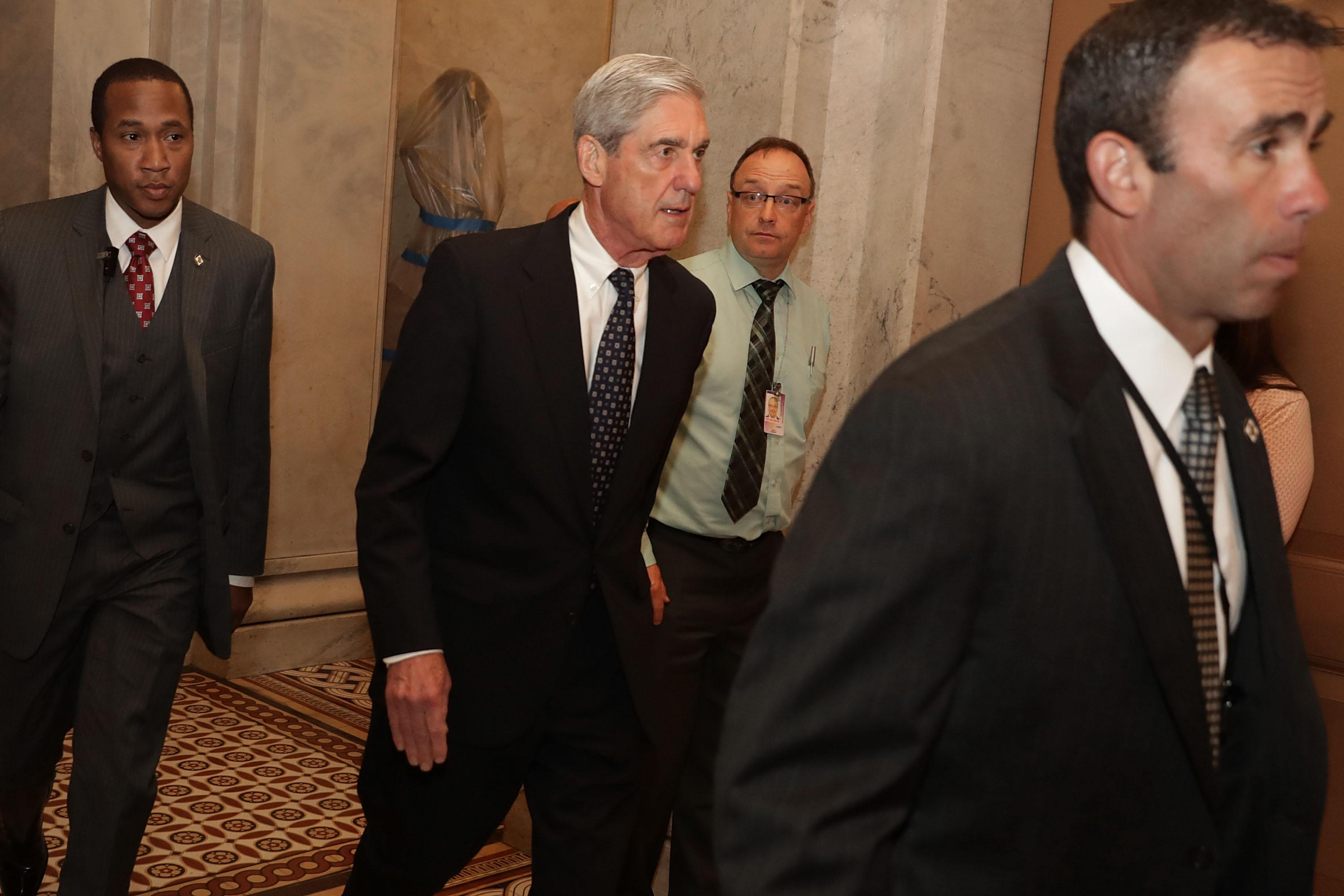 Former FBI Director Robert Mueller is surrounded by security and staff as he leaves a meeting with senators at the U.S. Capitol June 21, 2017 in Washington, DC.