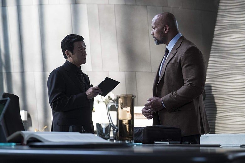 Chin Han, holding a black iPad, stands in conversation with Dwayne Johnson.