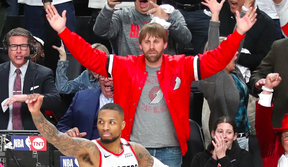 A bearded fan in a red Blazers jacket spreads his arms serenely behind Lillard.