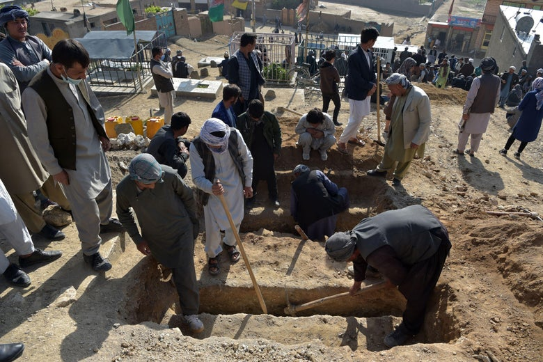 Shiite mourners and relatives dig graves for girls, who died in yesterday's multiple blasts outside a girls' school, during the burial at a desolate hilltop cemetery in Dasht-e-Barchi on the outskirts of Kabul on May 9, 2021.
