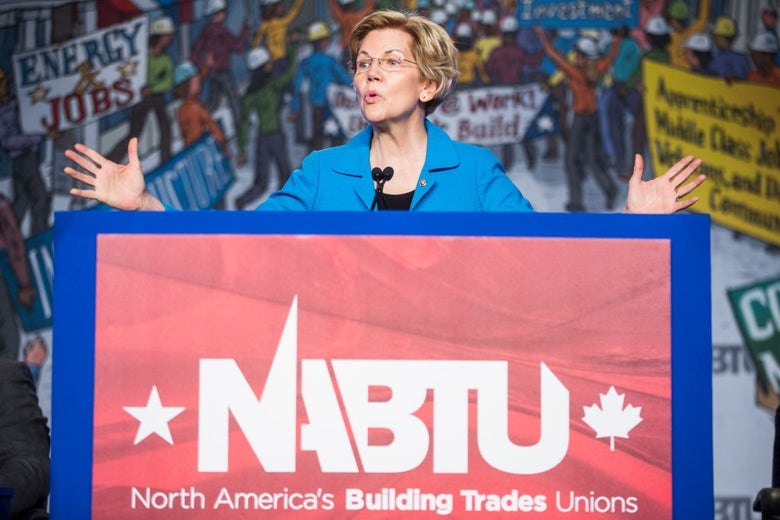 Warren, wearing a blue suit jacket, gestures with both hands from a lectern against a backdrop of drawings of workers wearing hard hats.
