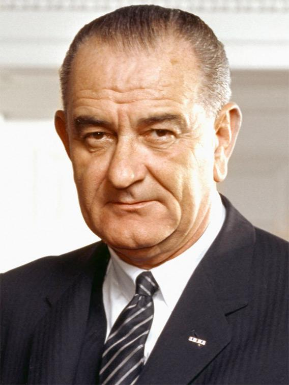 Photo portrait of President Lyndon B. Johnson in the Oval Office, leaning on a chair.
