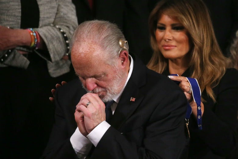 Limbaugh bows his head and clasps his hands together as Melania Trump stands behind him and prepares to put the medal around his neck.