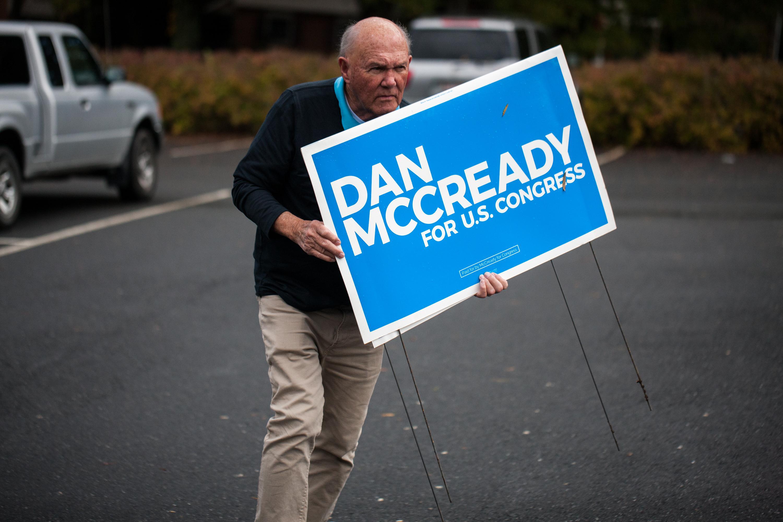 "A man holding a ""Dan McCready for U.S. Congress"" sign."