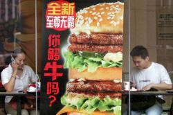 Customers finish their meal at a branch of McDonalds in Beijing, 20 June 2006.