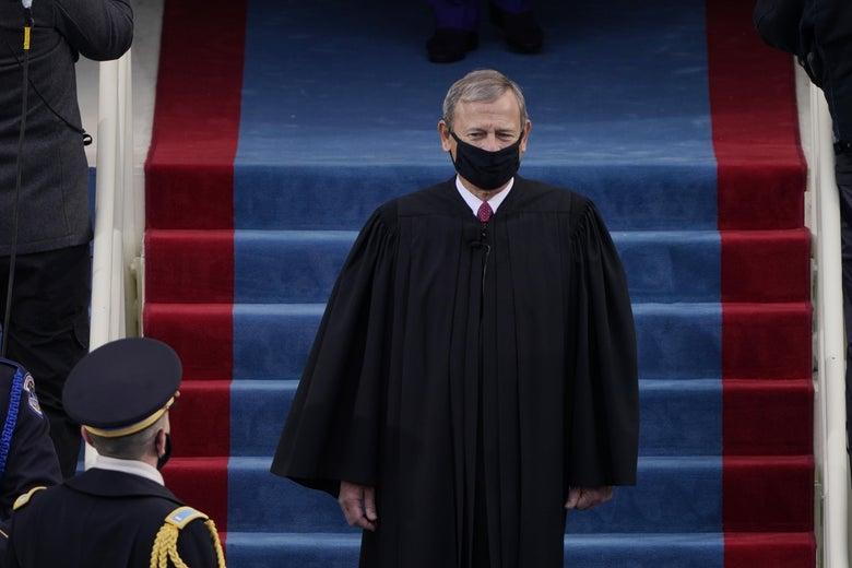 Chief Justice John Roberts wearing his judicial robe and a black mask.