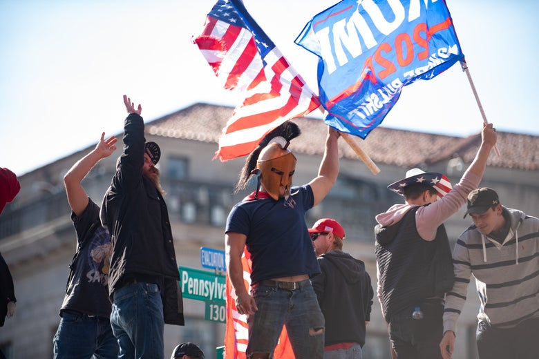 A man wearing a homemade Spartan helmet waves a flag among thousands of Trump loyalists who converged on Washington DC on Saturday for the Million MAGA March.