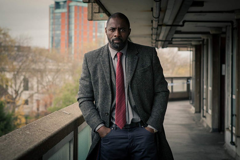Idris Elba stands with his hands in his pockets.