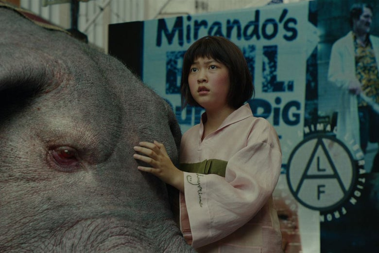 In a scene from Okja, Ahn Seo-hyun hugs her superpig protectively.