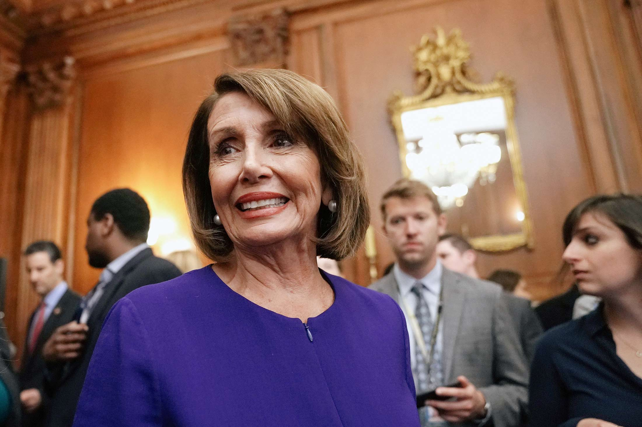 Nancy Pelosi wearing a blue jacket in a wood paneled room of the U.S. Capitol building surrounded by men in suits in the background.