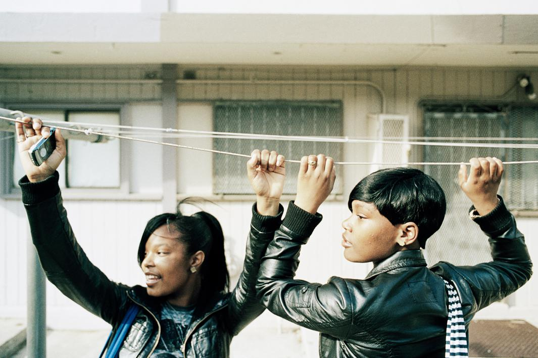 "'Ra Ra,"" left, and 'Mo Drama,' right, hang from the laundry lines in the Hunters View housing projects while waiting for a friend to catch up with them."