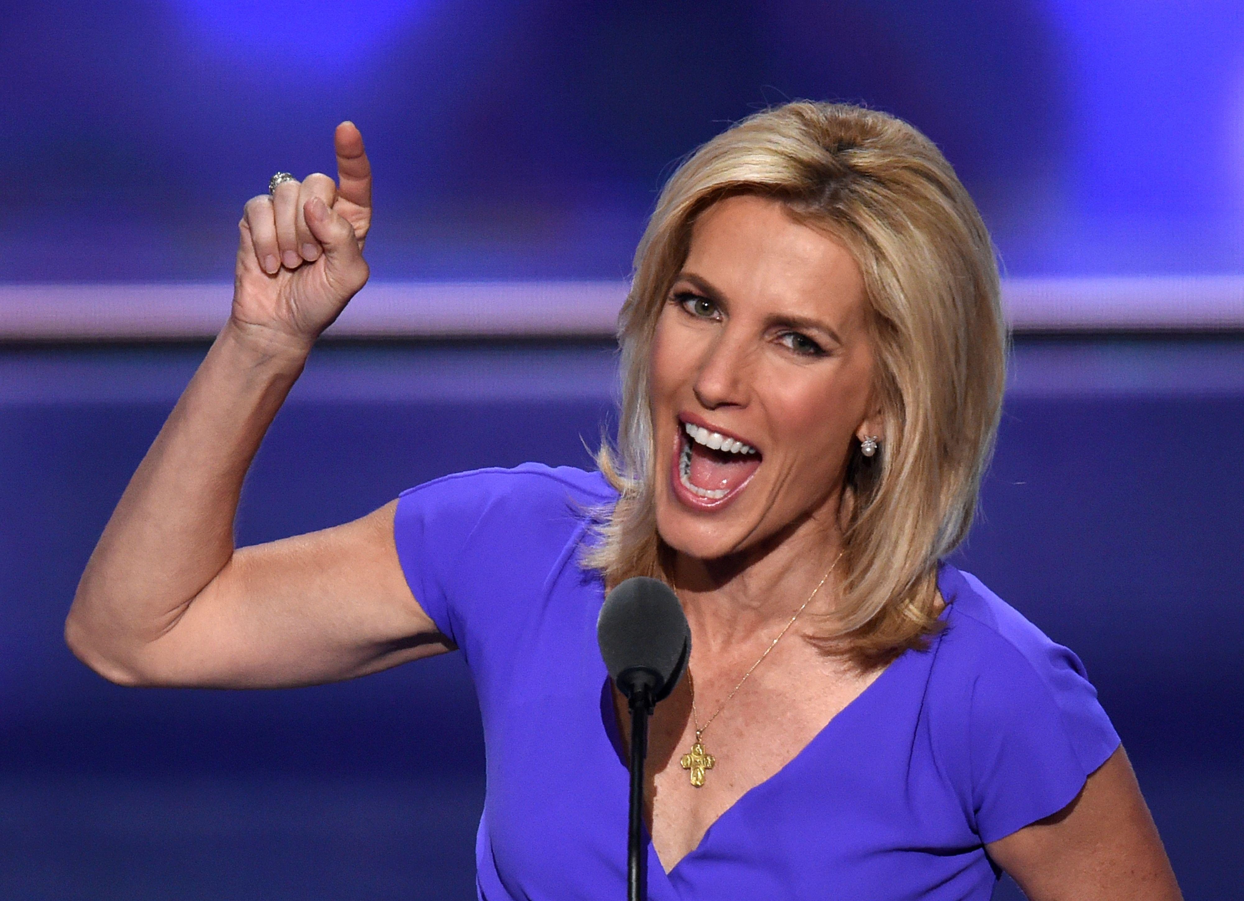 Ingraham smiles widely and points upward while standing behind a podium on a stage.