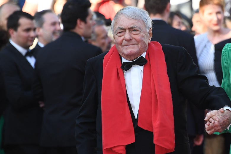Claude Lanzmann on a red carpet, wearing a tuxedo and a red scarf
