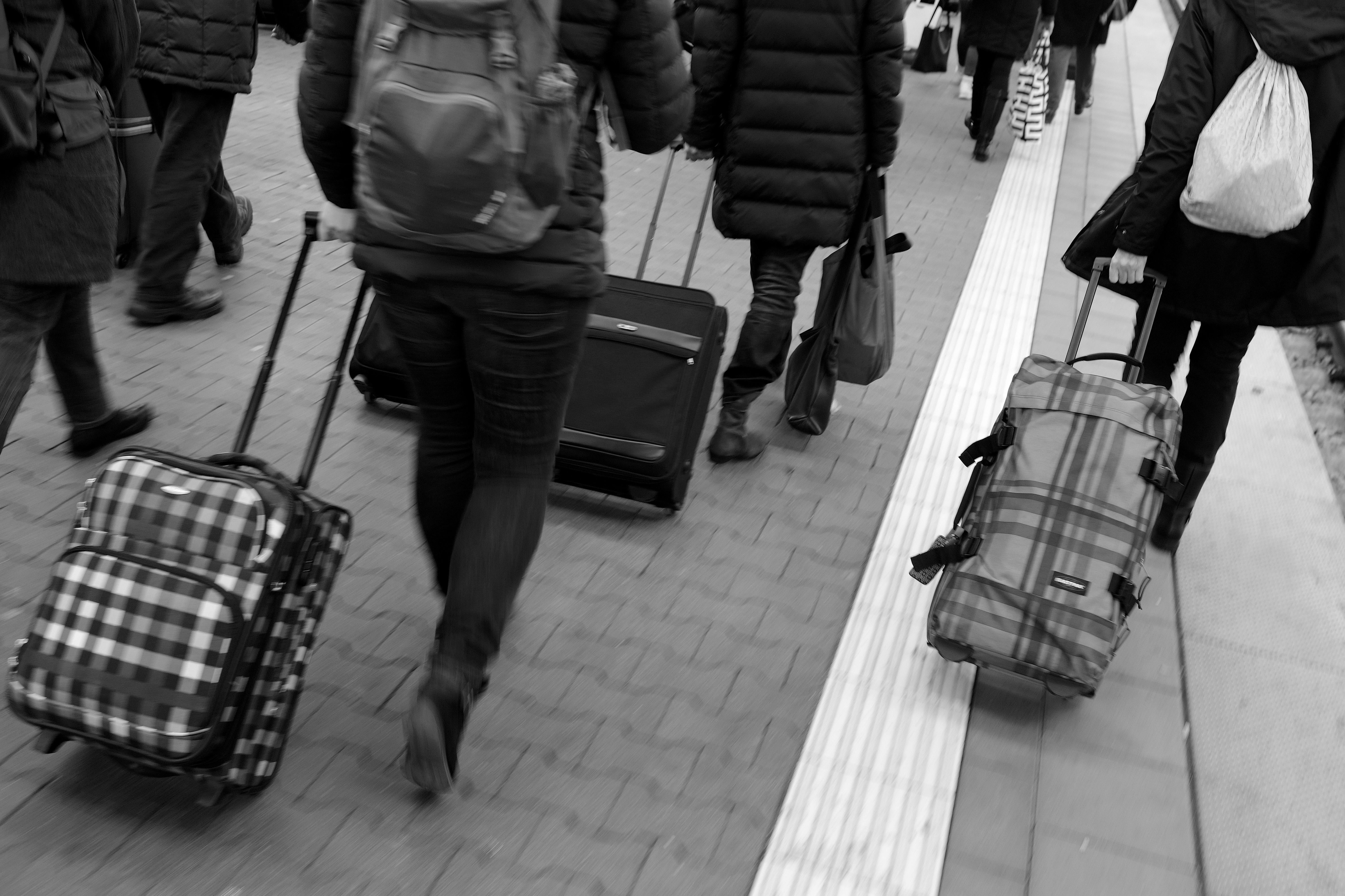 MUNICH, GERMANY - DECEMBER 15:  (EDITOR'S NOTE: Image has been shot in black and white. Color version not available.) Passengers pull their suitcases on a platform after arriving on a train of German state railway carrier Deutsche Bahn at Hauptbahnhof main railway station on December 15, 2017 in Munich, Germany. The season before Christmas is always a busy annual travel period across Germany. (Photo by Sean Gallup/Getty Images)