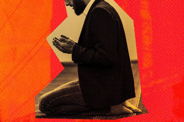 A young Muslim man wearing a suit and kneeling in prayer.