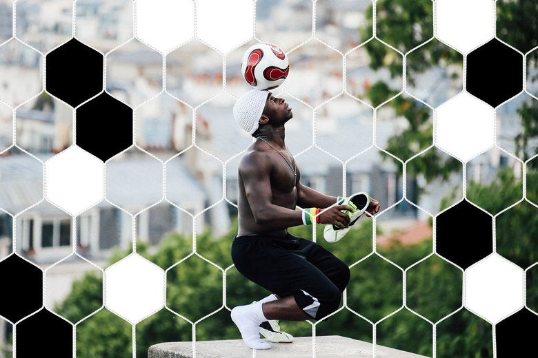 Iya Traore, a former professional football player, balances a football on his head as he performs for visitors in the Montmartre area of Paris.