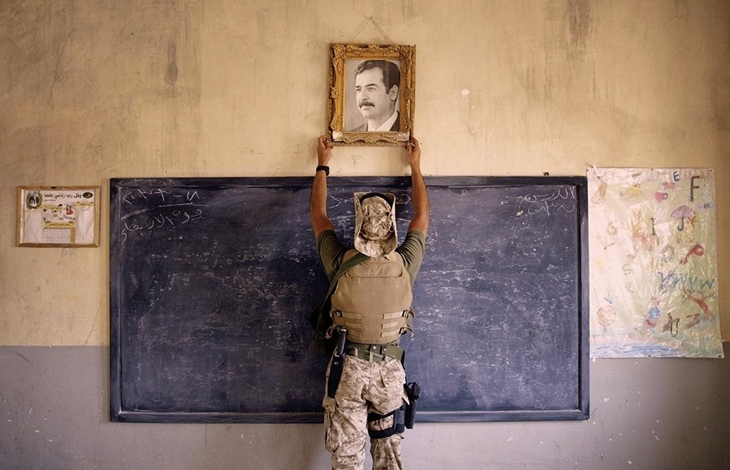 A Marine pulls down a picture of Saddam Hussein at a school on April 16, 2003, in Al-Kut, Iraq. U.S. troops went to schools and other facilities looking for weapons caches and unexploded bombs in preparation for removing and neutralizing them.