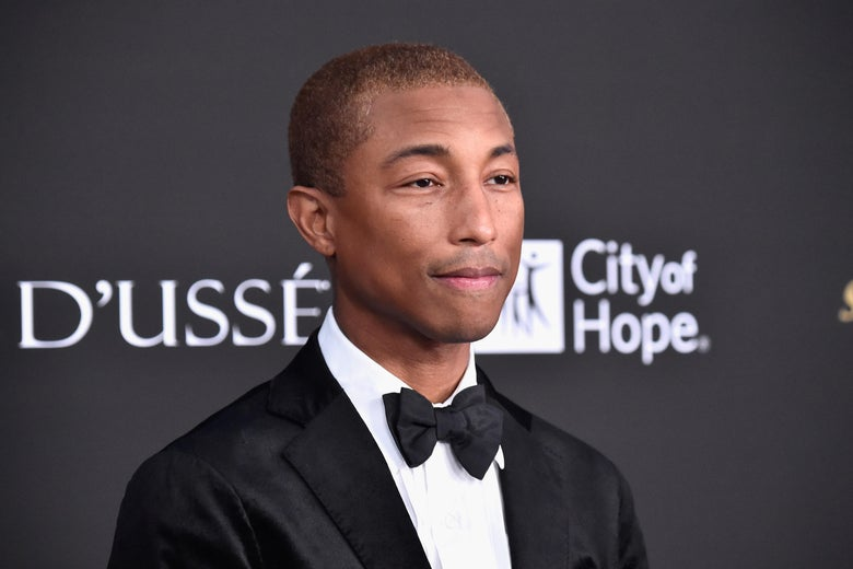 Pharrell Williams wears a black suit and bowtie.