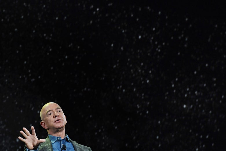 Jeff Bezos raises one hand while speaking, in front of a background of stars.