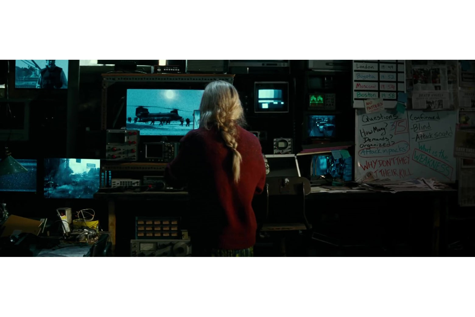 Emily Blunt standing in front of crazy scrawled whiteboard notes about the creatures attacking.
