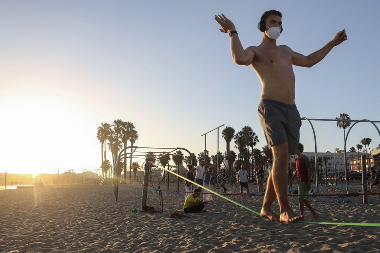 A man slacklines while wearing a face mask on Santa Monica beach amid the COVID-19 pandemic on July 2, 2020 in Santa Monica, California. Beginning July 3, Los Angeles County beaches and piers will be closed through the July 4th holiday weekend amid some reinstated restrictions intended to slow the spread of the coronavirus.