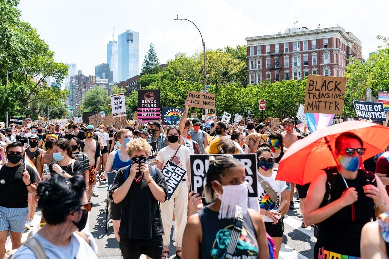 """Protesters hold up signs that say things like, """"Black Trans Lives Matter"""" and """"Queer Power."""""""
