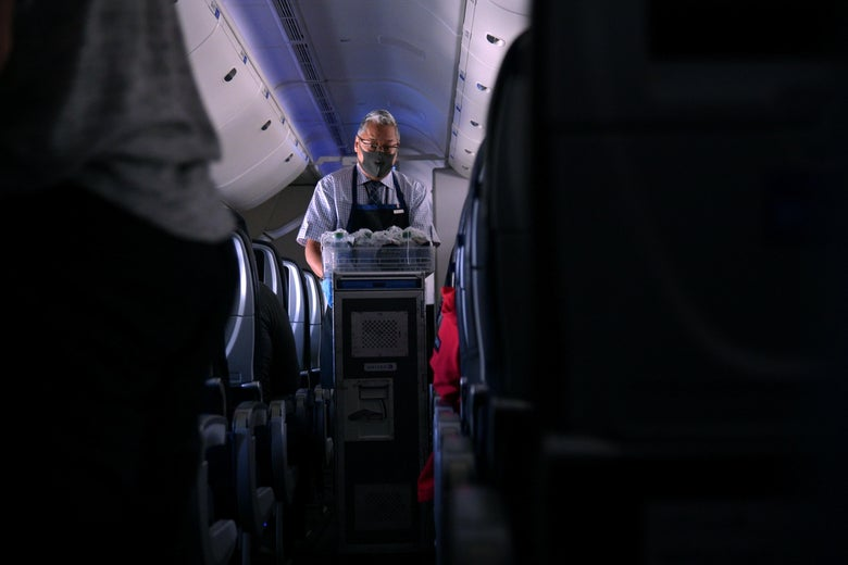 A masked flight attendant pushes a cart down an aisle on a plane as he passes out refreshments.