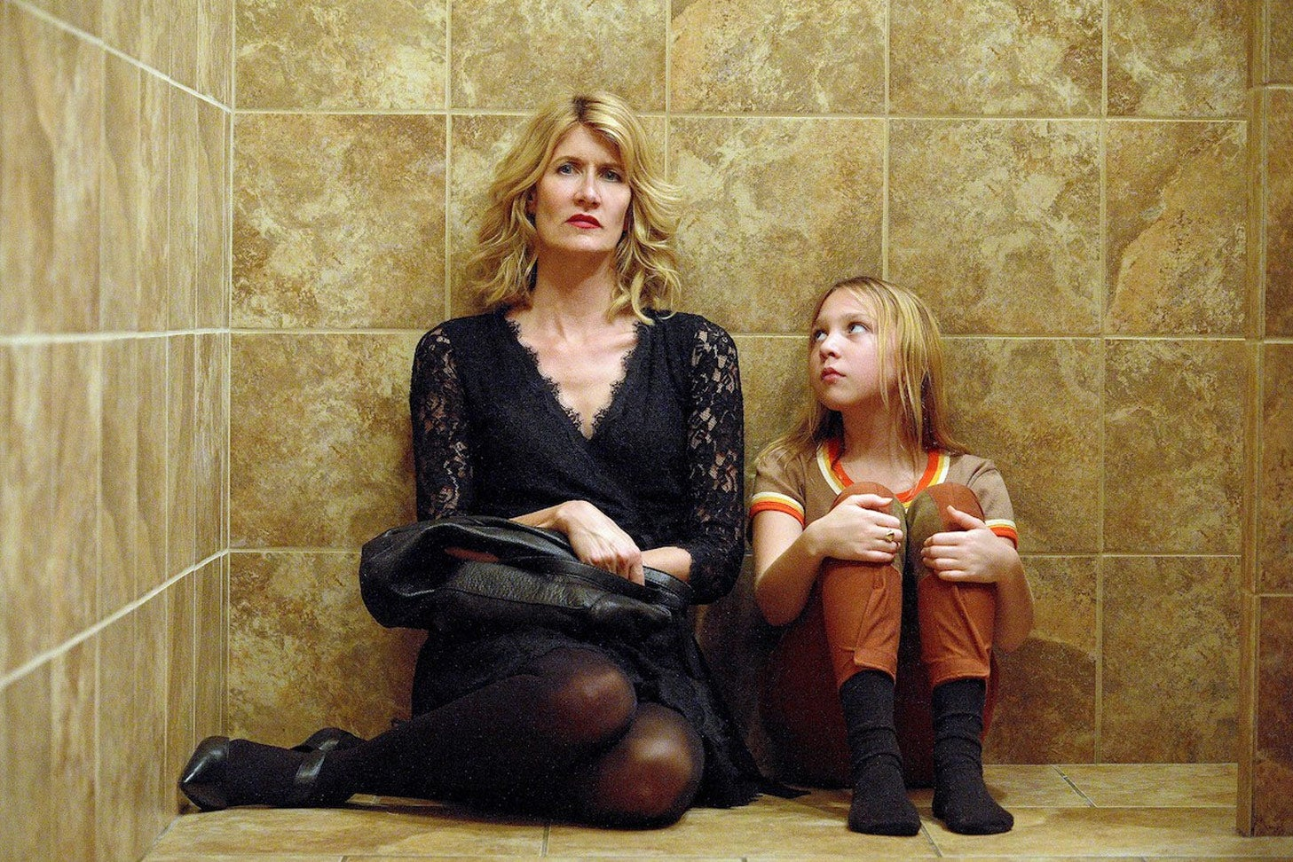 Laura Dern and Isabelle Nélisse sit next to each other on a tile floor in this promotional image for The Tale.