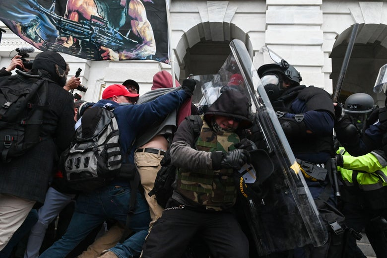 Pro-Trump rioters clash with police in riot gear.