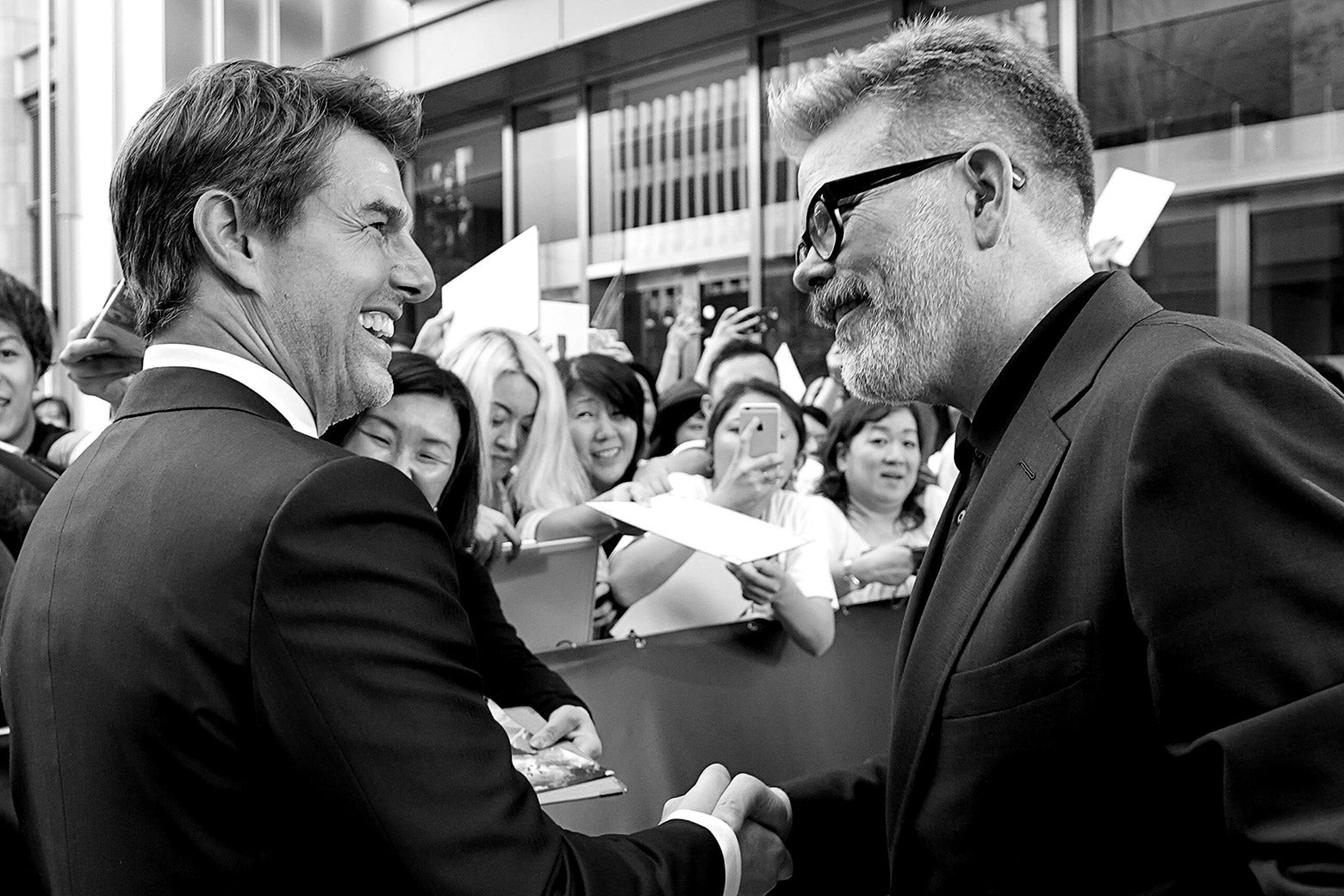 Tom Cruise and Christopher McQuarrie shake hands.