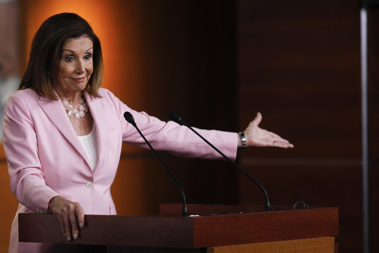 Nancy Pelosi gestures while behind a podium.