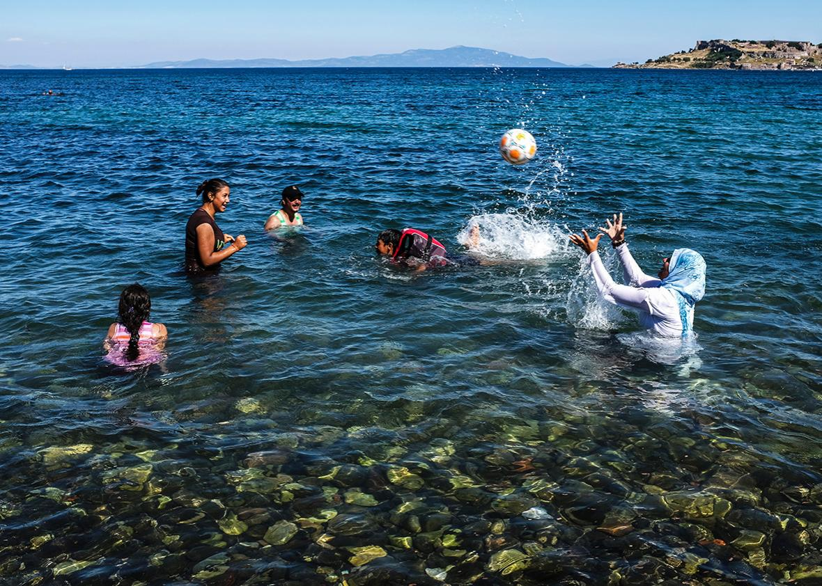 Women and children play in the water off the island of Lesbos on June 12.