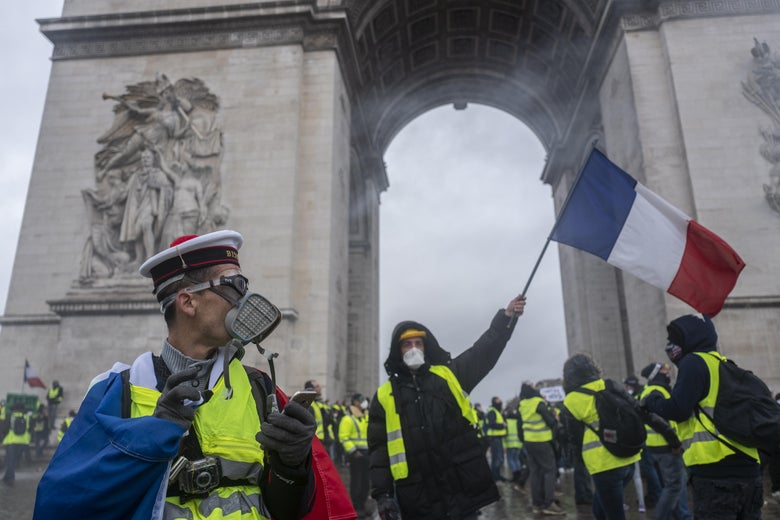 "Protesters and riot police at the Arc de Triomphe during ""Yellow Vest"" protests"