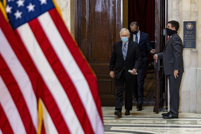 A man wearing a face mask opens a door to let in McConnell and another man, both of whom are wearing face masks. A U.S. flag is seen in the foreground.