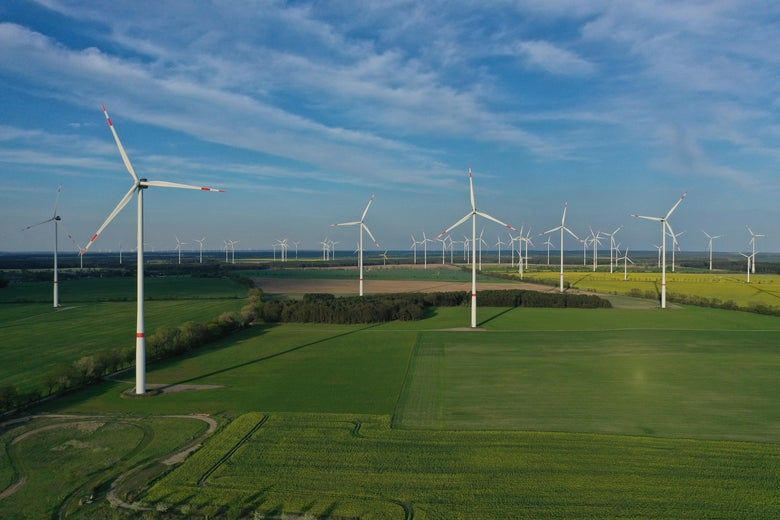 Wind turbines spin in an agricultural field.