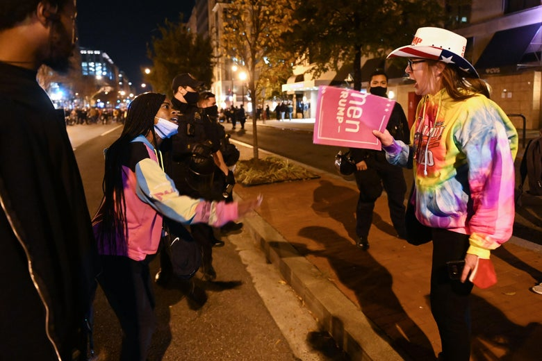 Two people shouting at each other: A Black woman with a mask pulled down to her chin and a white woman with a Women for Trump sign, in American flag cowboy hat and tyedye sweater