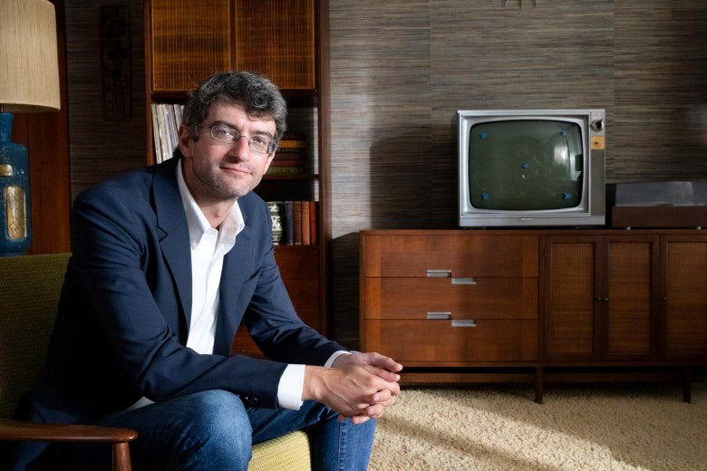 Leon Neyfakh sits in a chair in front of a credenza and old-fashioned TV.