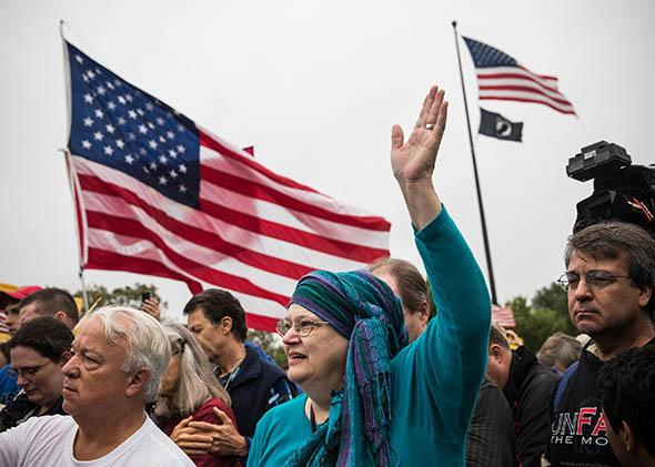 A woman raises her hand in prayer at a rally centered around reopening national memorials closed by the government shutdown, supported by military veterans, Tea Party.