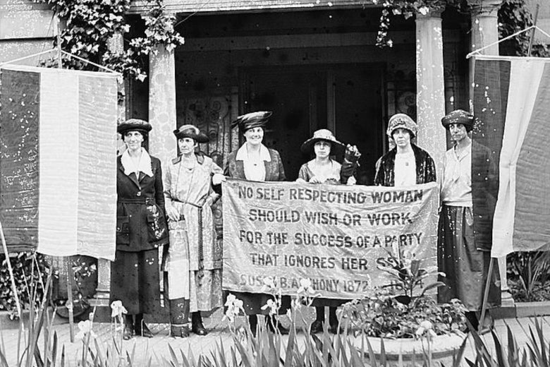 Suffragists Sue White, Benigna Green Kalb, Jas Rector, Mary Dubrow, Alice Paul, and Elizabeth Kalb stand in front of the National Woman's Party Washington HQ holding a sign with a Susan B. Anthony quote.