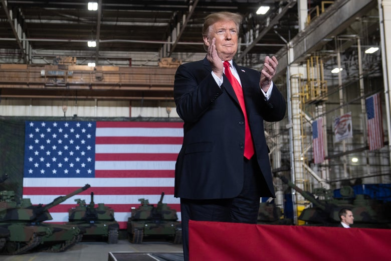 Trump stands in front of a giant American flag and a number of tanks.
