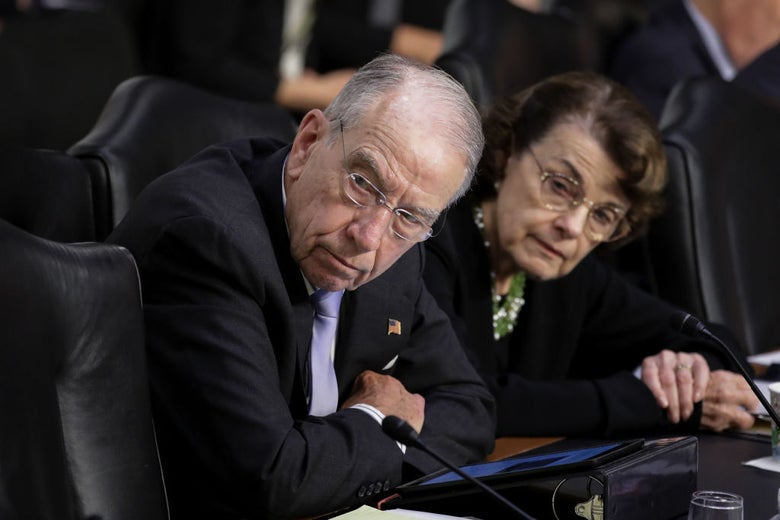 Grassley and Feinstein look to their right while seated at a committee hearing.