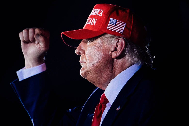 Trump in profile, wearing a red MAGA hat and raising his fist